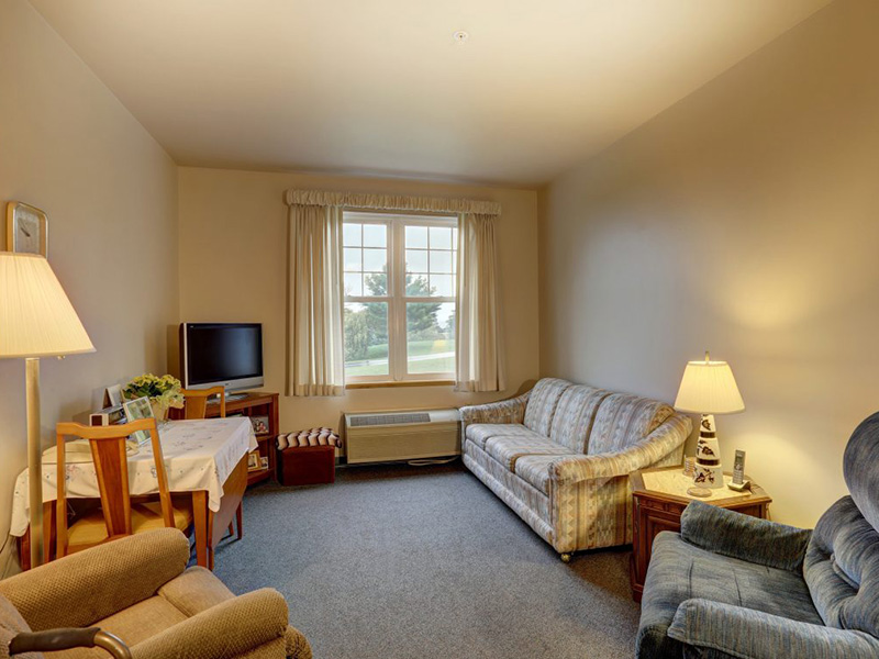 Resident living space with comfortable seating and a beautiful view of the walking path and trees from the window