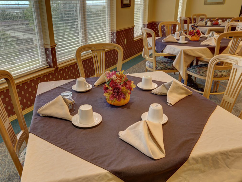Resident dining room with neatly set tables with linen table covers and napkins