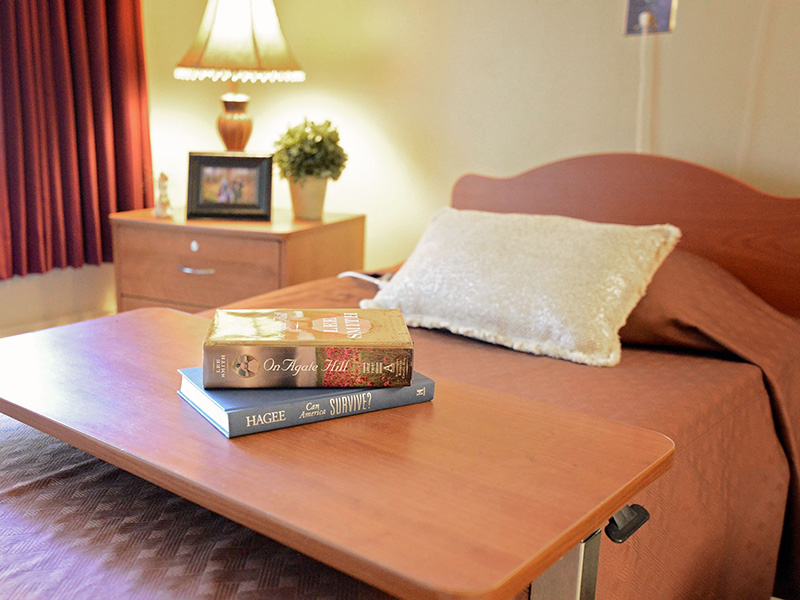 Resident bed with a nightstand and a nicely made bed with books on the side table.