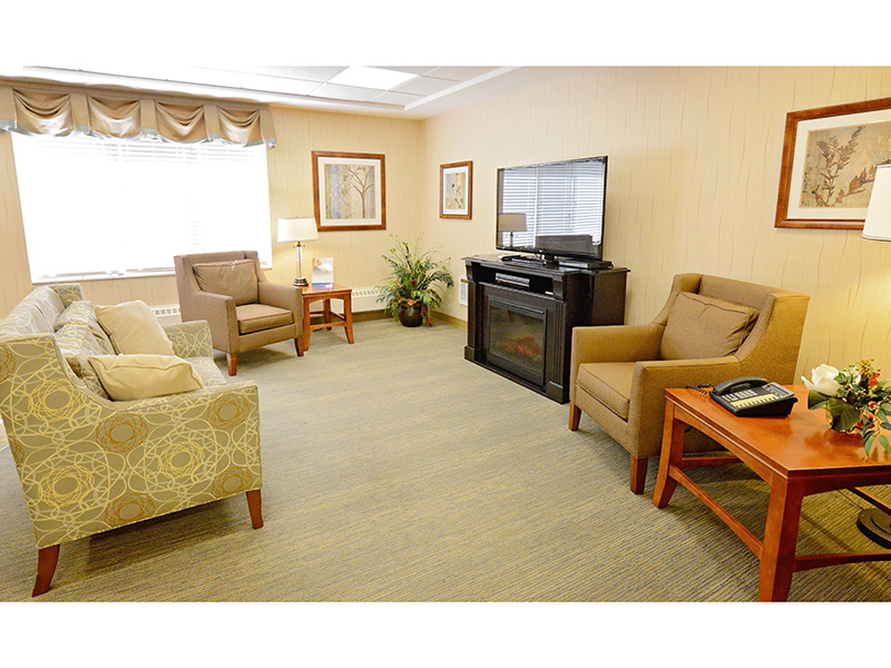 Resident lounge space with several options for seating in front of a flat screen television.