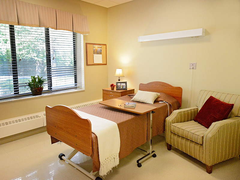Resident room with the bed beside a window with a beautiful view of the lush grass and full tree.