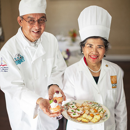 two chefs wearing full chef gear holding an appetizer plate