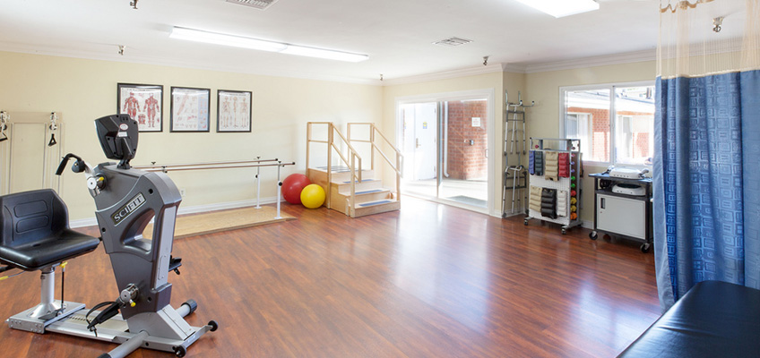 rehabilitation room with various equipment and a sliding glass door