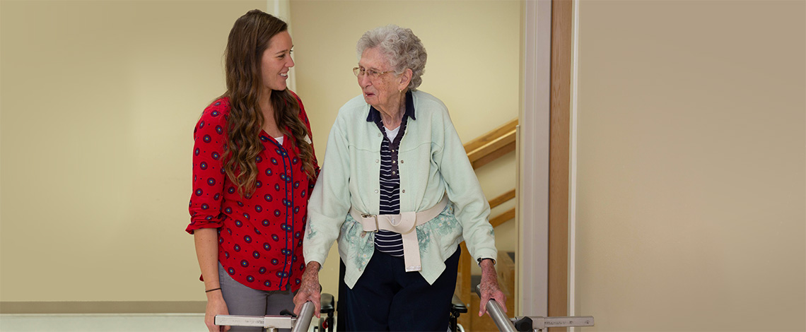 A nurse walking with a resident down the hall