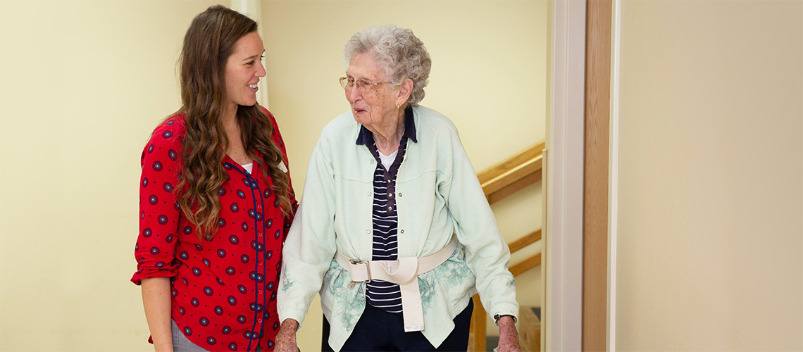 A nurse walking with a resident down the hallway