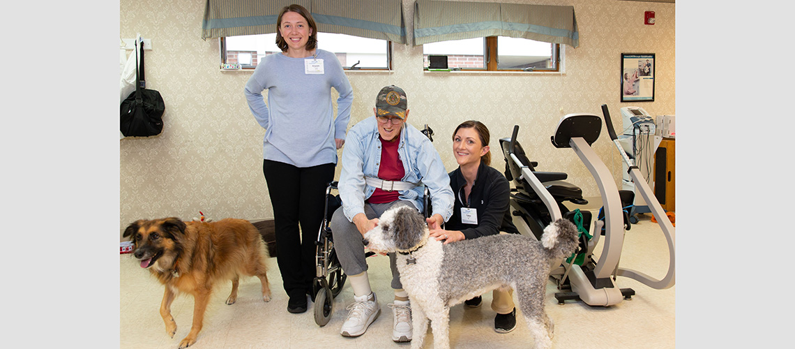 A couple nurses and a resident doing some therapy with happy dogs