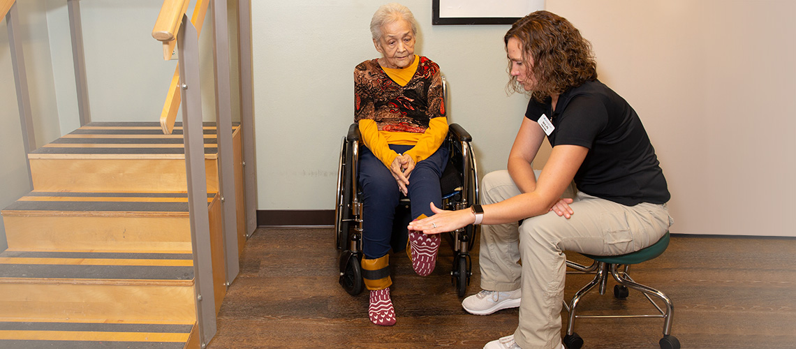 A nurse helping a resident with knee flexibility