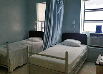Resident room with beds and a curtain that separates the beds for privacy
