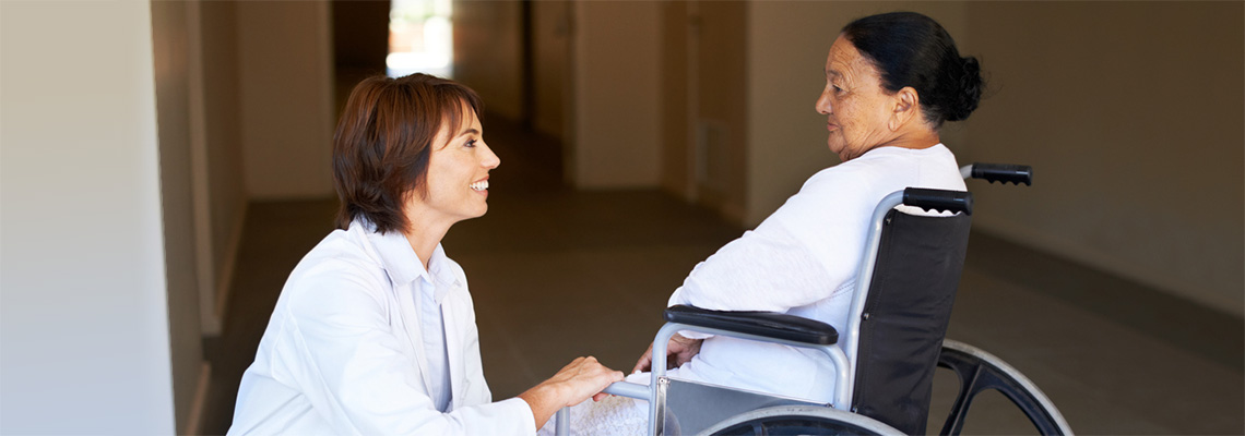 Nurse leaning down speaking to a patient in a wheelchair