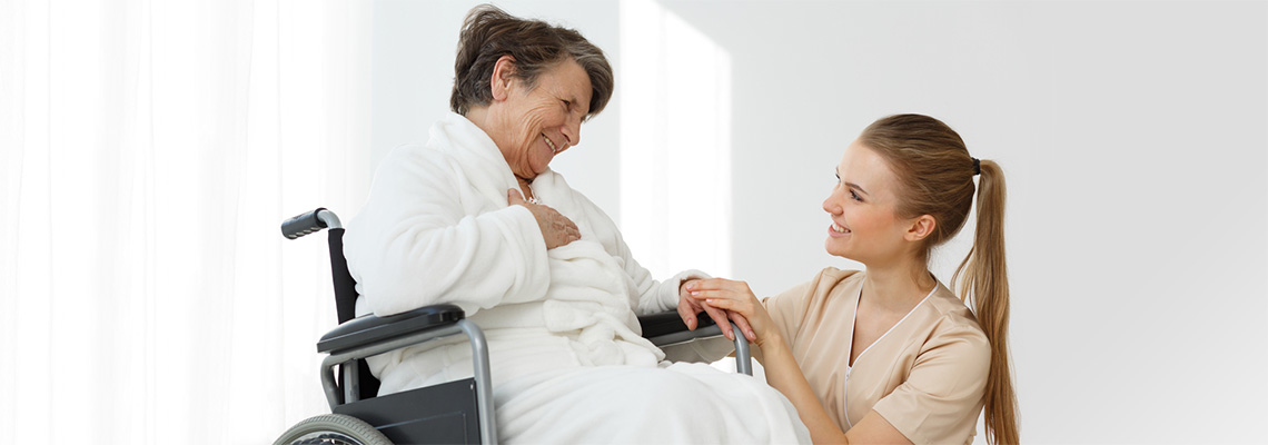 Young woman holding the hand of an elderly woman in a wheelchair