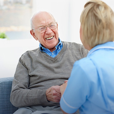 elderly gentleman having a good laugh with the nurse