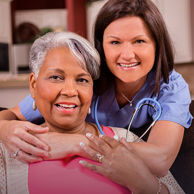nurse with stethoscope hugging a seated resident
