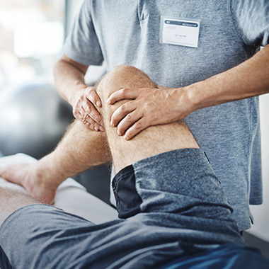 physical therapist working on therapy on a resident's knee