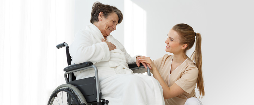 sweet young nurse kneeling, holding a resident's hand inquiring how she is doing