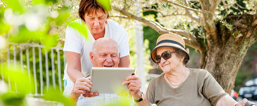 man smiling and looking at an ipad while family members look on