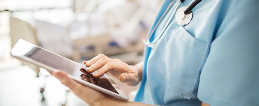 close up of nurse with stethoscope using an ipad