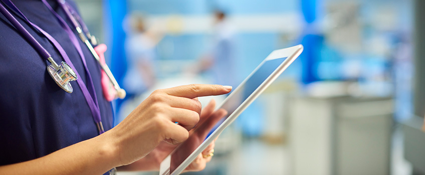 close up of nurse using an ipad for work