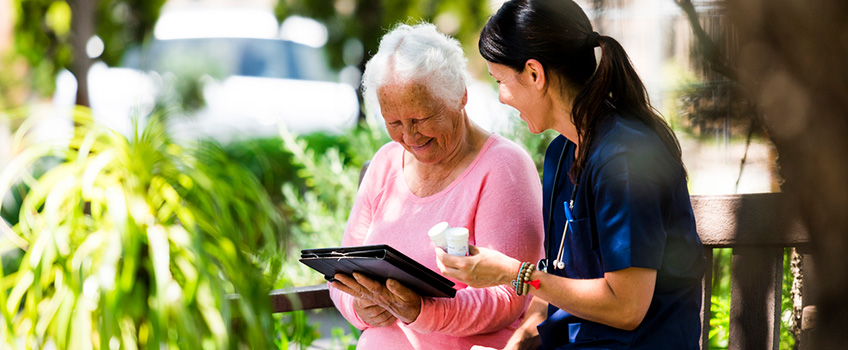 resident looking at a photo album while a nurse gives her medicine