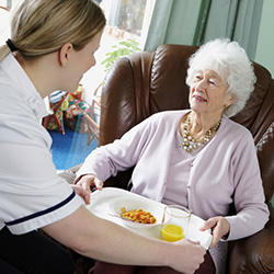 Patient being brought food by a nurse
