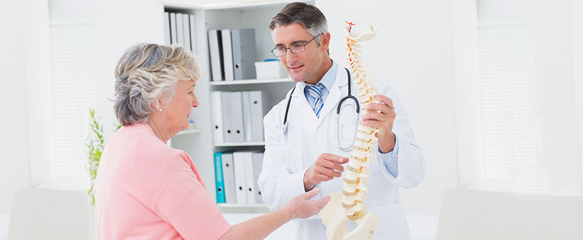 Doctor and patient looking at a spine example
