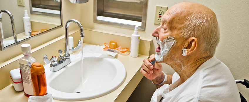 A senior shaving his face in front of a sink with running water.