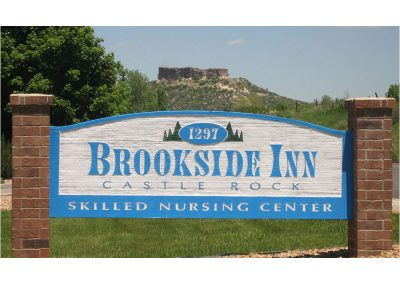 Brookside Inn's sign out front with the address and the mountain in the background.