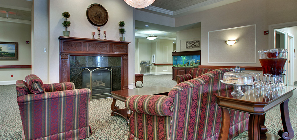 Fireplace and seating area with upholstered chairs and sofa and refreshments ready for guests