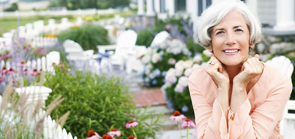 Silver haired woman sitting in a beautiful garden with a white picket fence and flowering plants