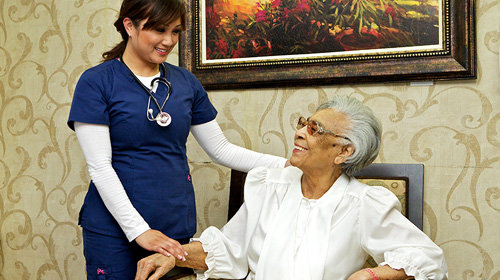 Nurse with her hand on a residents hand as they smile at each other