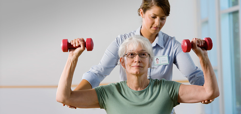 Rehab staff assisting a woman with rehab exercises