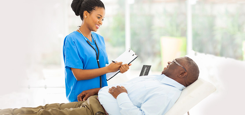 A nurse holding a clipboard smiling down at a patient lying in bed