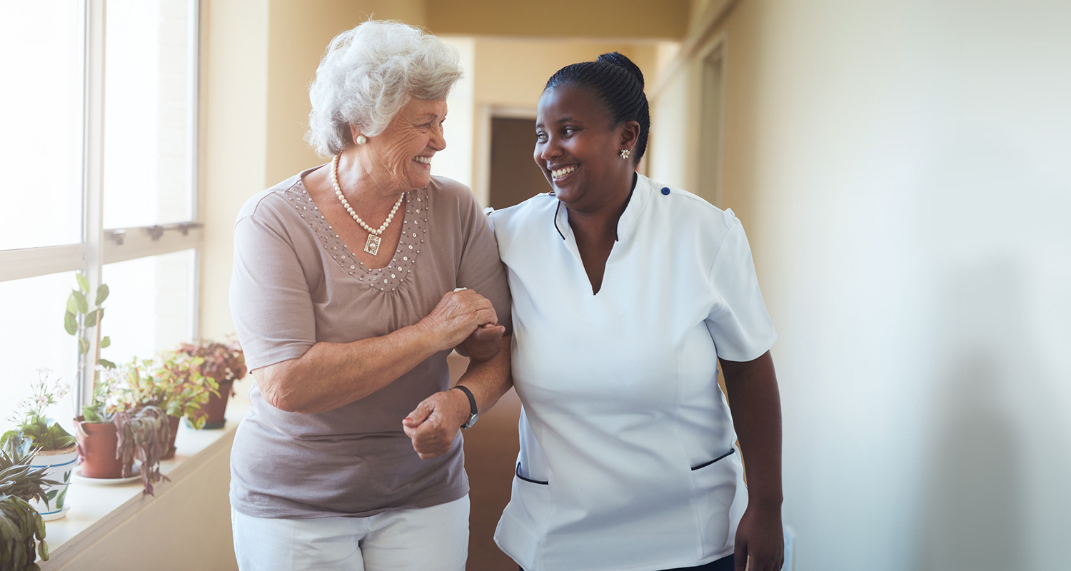 Nurse and resident walking arm in arm down a hallway