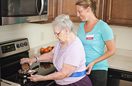Therapist assisting a resident with cooking for herself