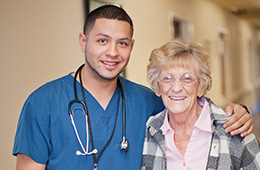 Male nurse and female resident standing in the hallway