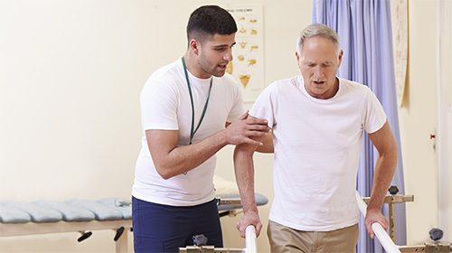 A staff member assisting a patient with walking.