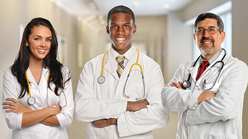 Three doctors standing together in a group smiling.