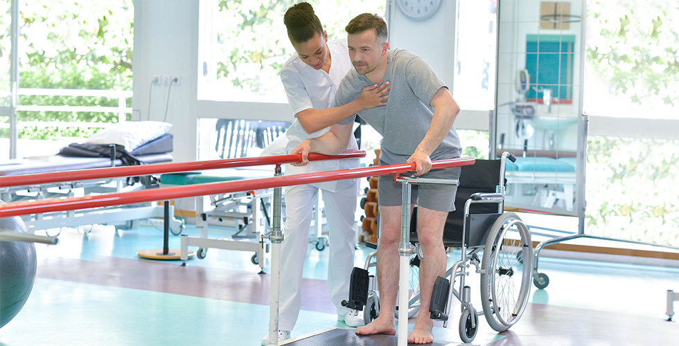 A brain injury program patient being assisted by rehabilitation staff.