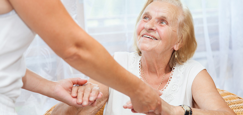 elderly woman looking up at her caregiver and holding her hand