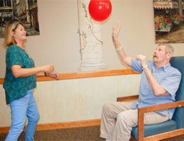 A resident and staff member doing rehab exercises.