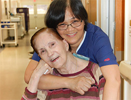 A nurse and resident hugging each other.