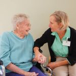 A staff member holding the hand of a resident as they talk to each other.