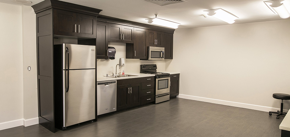 kitchen area with stainless steal appliances and dark wood cabinets