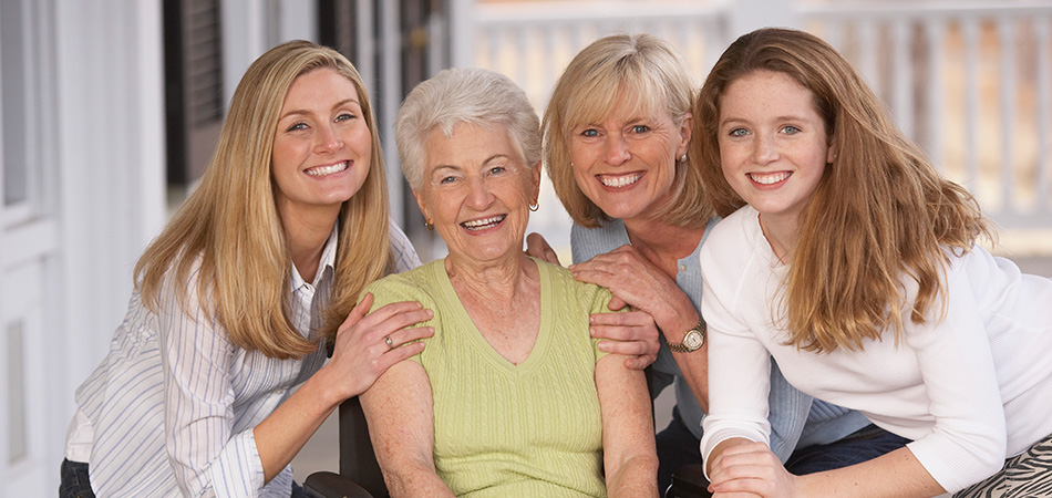 A family of women gathered together smiling