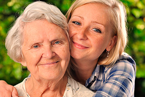 Grandmother and granddaughter smiling together outside