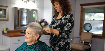 A salon stylist doing a residents hair.