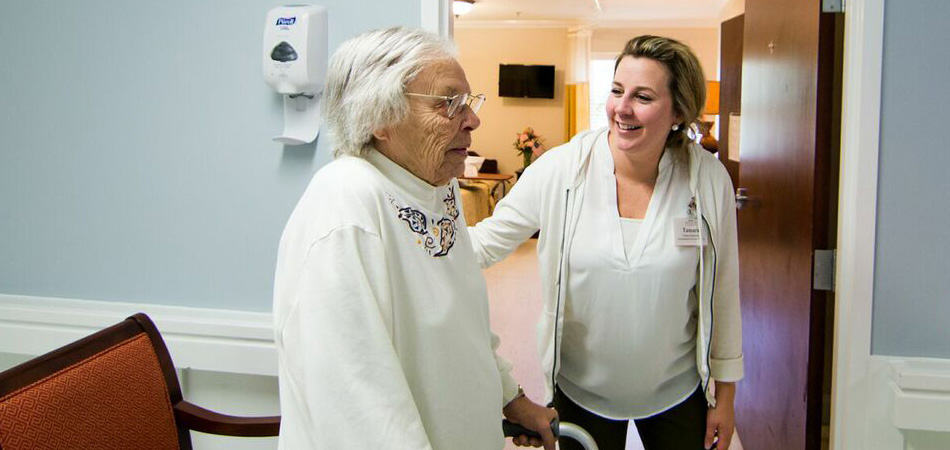 resident standing with aide from a nurse