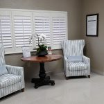 lovely upholstered chairs in a waiting area with a table with a live orchid and plantation shutters on the windows