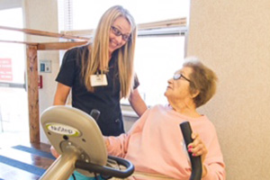 therapist working with a resident on an exercise machine