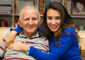 Young woman visiting with an elderly gentleman in the library
