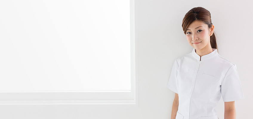 smiling nurse standing against a wall next to window